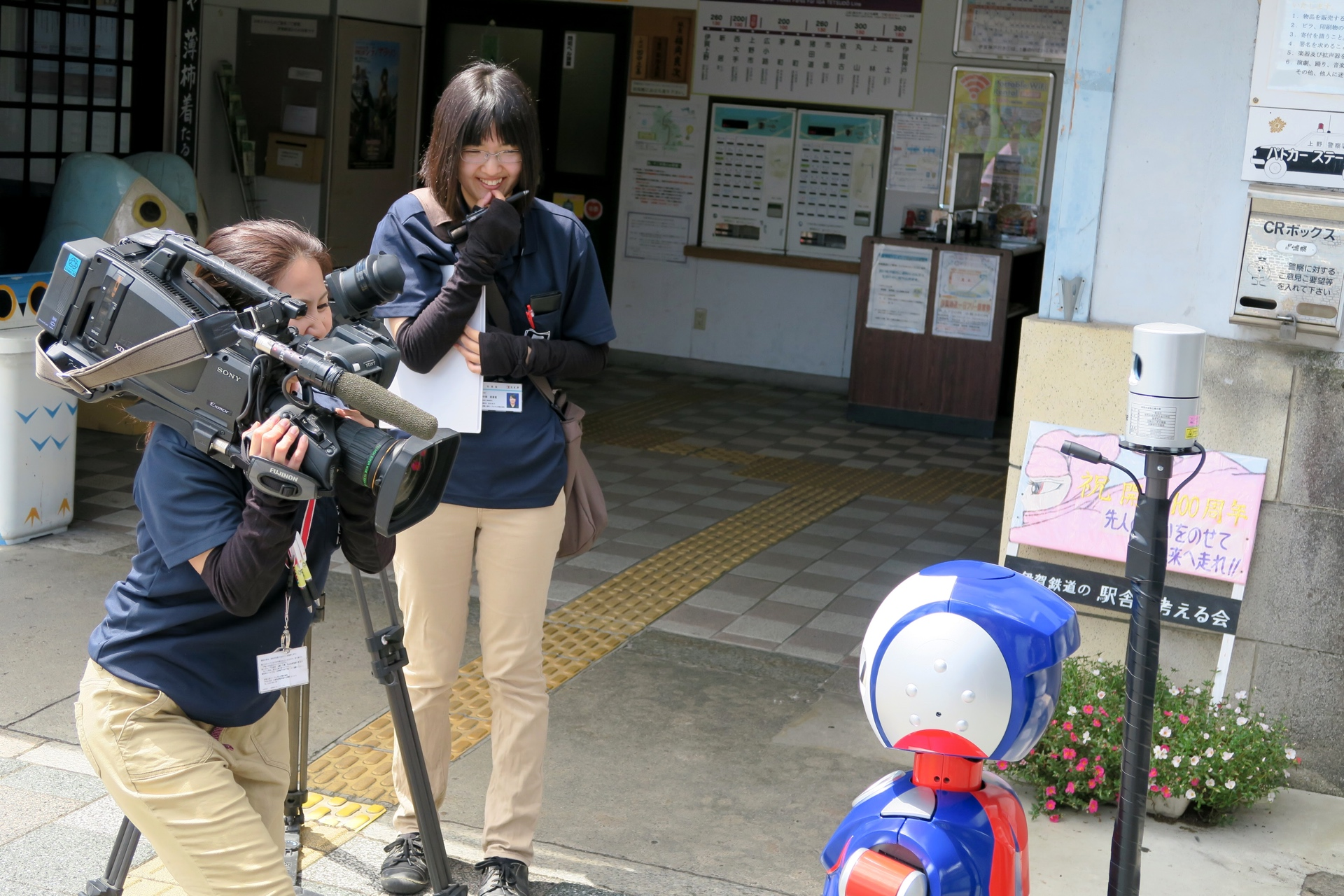 Local TV staff engaging with Robovie.