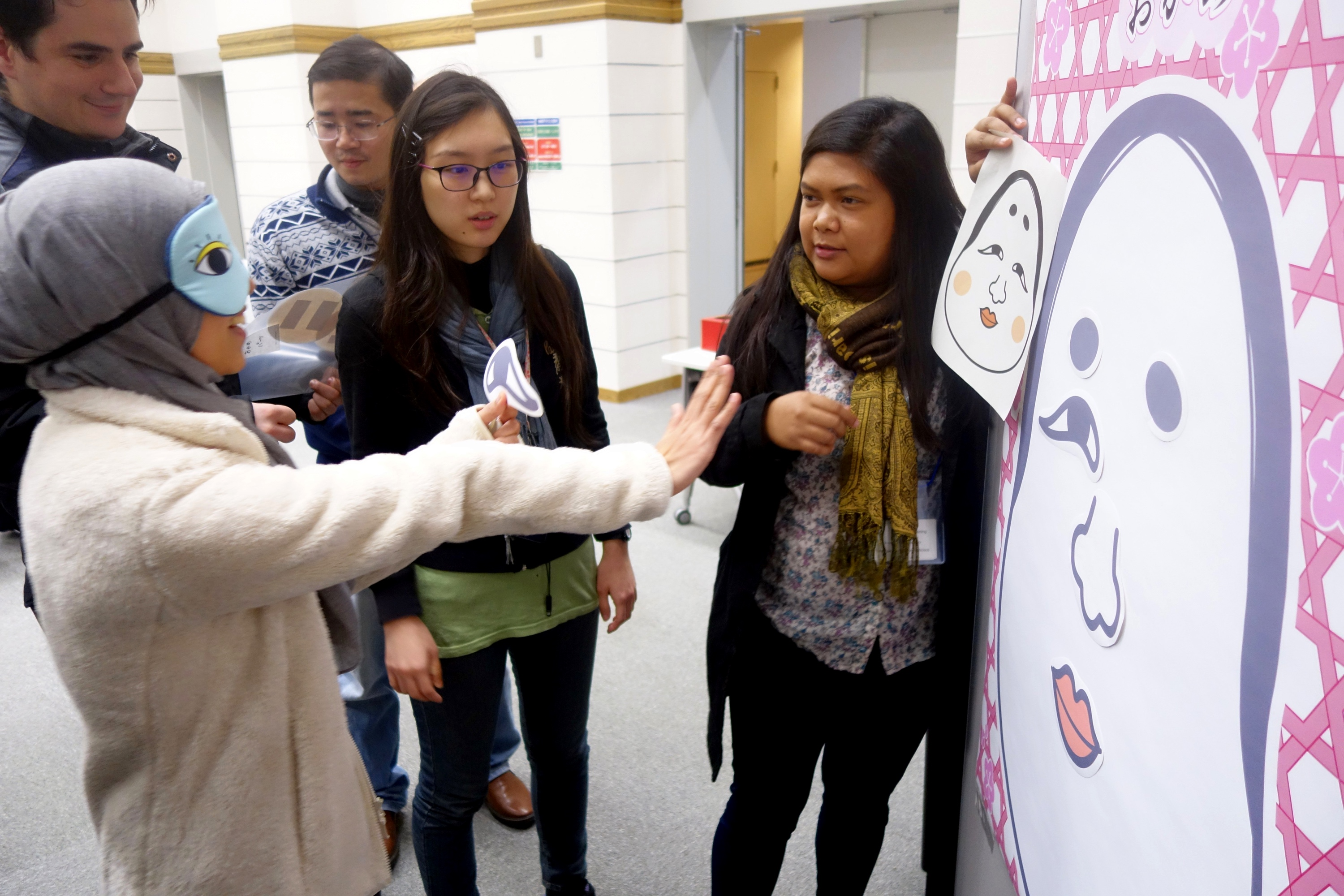 A student is instructed to pin an eye on a helpless face at the NAIST Tea Time.