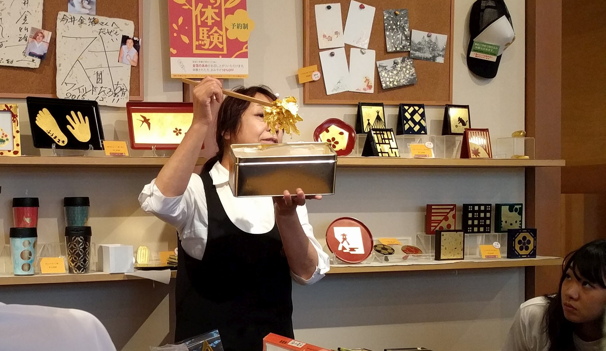 An instructor shows the gold leaves used for kinpaku (gold-plating), a traditional local industry, to a class of Japan TENT visitors